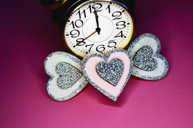 Budzik w kolorach tęczy lgbt i trzy małe serca na różowym i czarnym tle