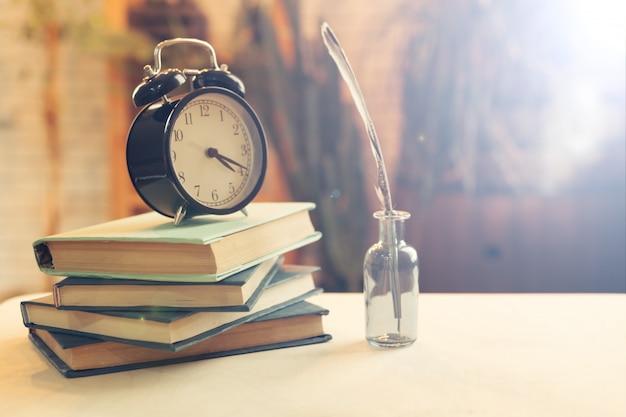 Budzik w pobliżu książek na stole