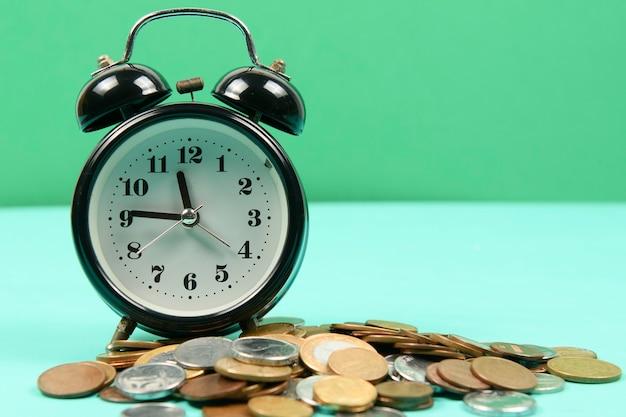 Budzik wraz z monetami przypominający o oszczędzaniu pieniędzy