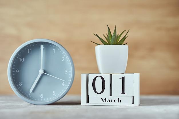 Budzik z datą kalendarza drewnianego bloku 1 marca i roślin na stole