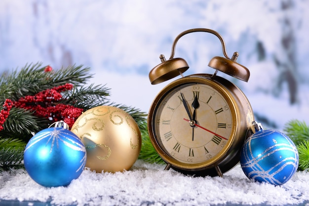 Budzik z dekoracjami świątecznymi na jasnym tle