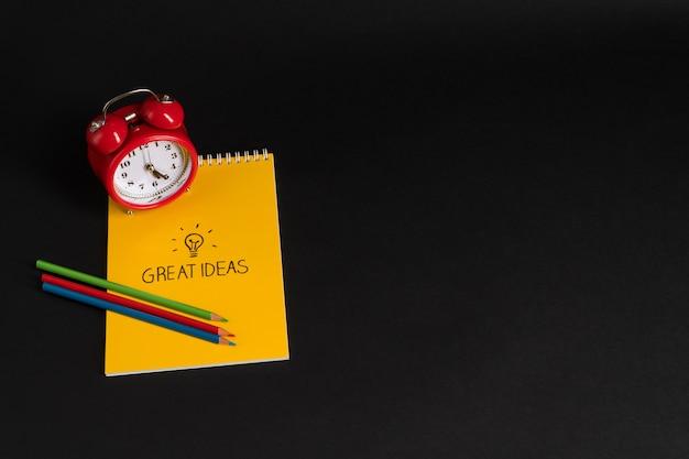 Budzik z notatnikiem i kredkami na czarnym tle powrót do szkoły świetne pomysły