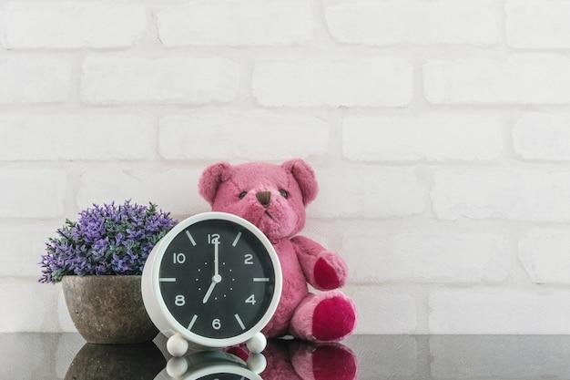 Budzik zbliżenie do dekoracji w 7 rano z lalką niedźwiedzia i roślin