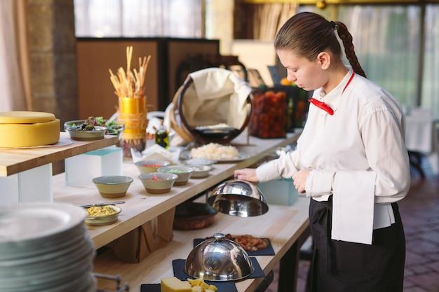 Bufet. kelner nakrywa do stołu.