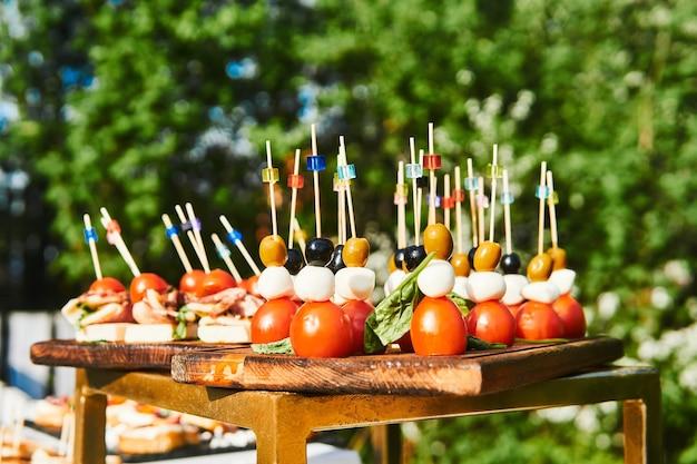 Bufet na świeżym powietrzu - kanapki na kijach koktajlowych z bliska na tle kwitnących drzew