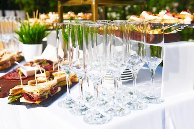 Bufet na świeżym powietrzu - puste szklanki na tle zimnych przekąsek na stole czekają na gości