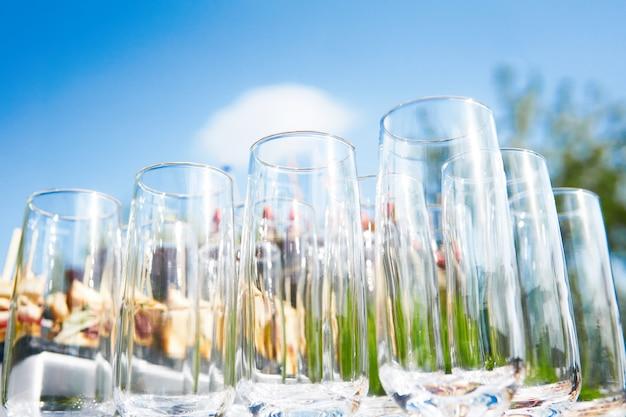 Bufet na świeżym powietrzu - puste szklanki na tle zimnych przekąsek na tle nieba czekają na gości