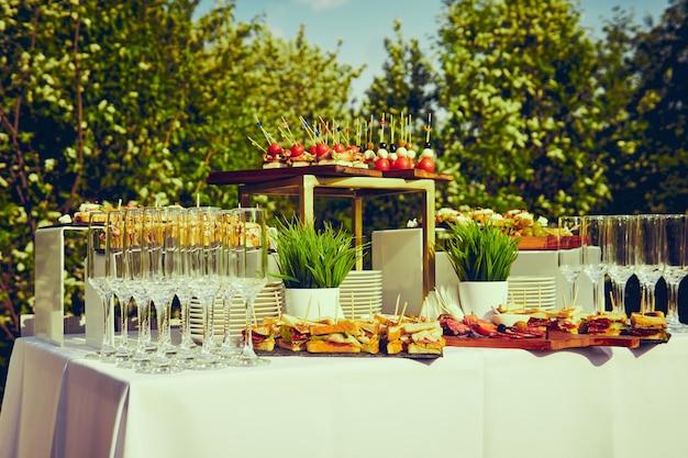 Bufet na świeżym powietrzu - stół z kanapkami i szklankami na tle kwitnących drzew i nieba