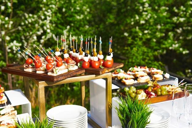 Bufet na świeżym powietrzu - stół z kanapkami na kijach koktajlowych na tle kwitnących drzew