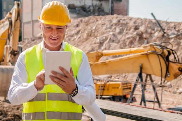 Builder działalności pracownika z cyfrowego tabletu na placu budowy