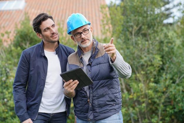 Builder przegląda plany na zewnątrz z właścicielami domów