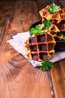 Bujne belgijskie gofry z warzywami i ziołami na drewnianym stole. pojęcie zdrowej diety i wegetarianizmu. ciemne zdjęcie w stylu rustykalnym. wolne miejsce na tekst.