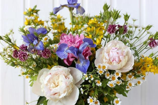 Bujny bukiet ogrodowy: piwonie, irysy, orlik i rumianek. kwiaty zbliżenie, selektywne focus.