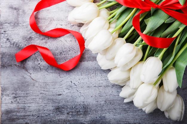 Bukiet białe tulipany z czerwoną wstążką