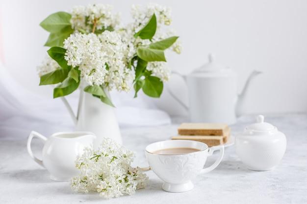 Bukiet białego bzu, filiżankę kawy i starą książkę