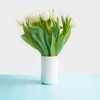 Bukiet białego tulipana w wazonie na niebiesko. dzień matki.