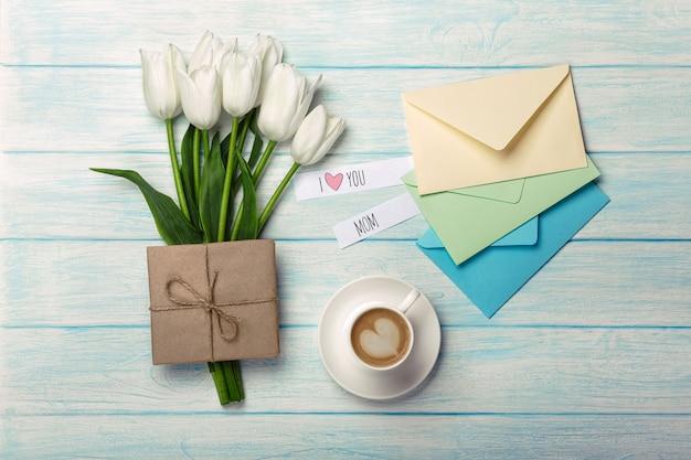 Bukiet biali tulipany, filiżanka kawy z miłości notatką i kolor koperty na błękitnych drewnianych deskach. dzień matki