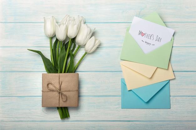 Bukiet biali tulipany z miłości notatką i kolor kopertami na błękitnych drewnianych deskach. dzień matki