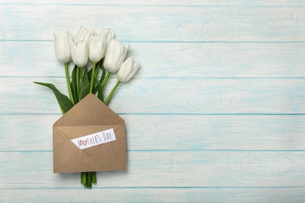 Bukiet biali tulipany z miłości notatką i kopertą na błękitnych drewnianych deskach. dzień matki