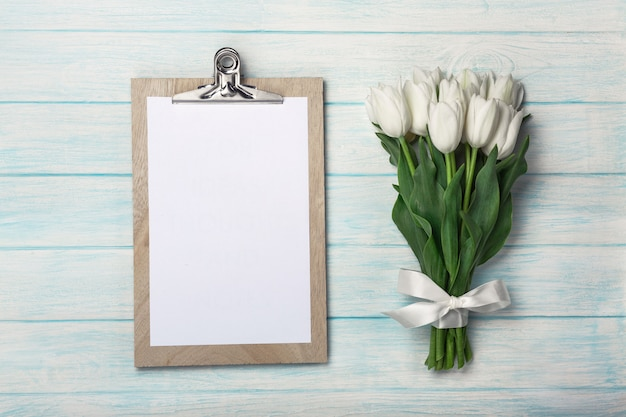 Bukiet biali tulipany z pastylką na błękitnych drewnianych deskach. dzień matki