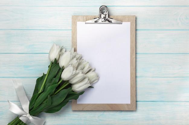 Bukiet biali tulipany z pastylką na błękitnych drewnianych deskach