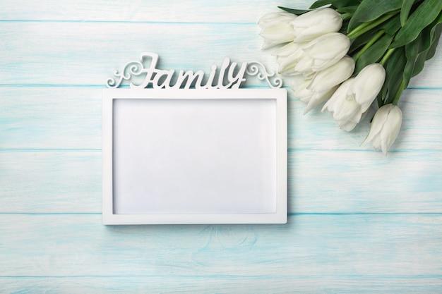 Bukiet biali tulipany z ramą dla inskrypci na błękitnych deskach. dzień matki