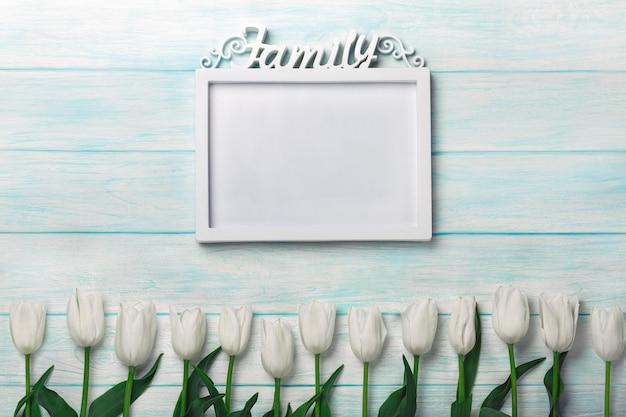 Bukiet biali tulipany z ramą dla inskrypci na błękitnych deskach