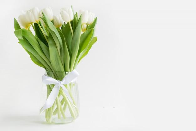 Bukiet biały tulipan w wazonie na bielu.