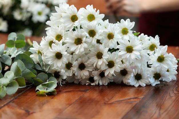 Bukiet białych chryzantem leży na drewnianym stole.
