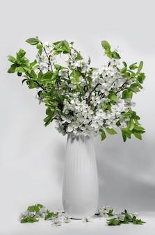Bukiet białych gałęzi czeremchy w ceramicznym białym dzbanku na białym stole. wiosna