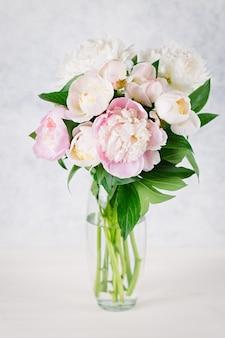 Bukiet białych i różowych piwonii w wazonie