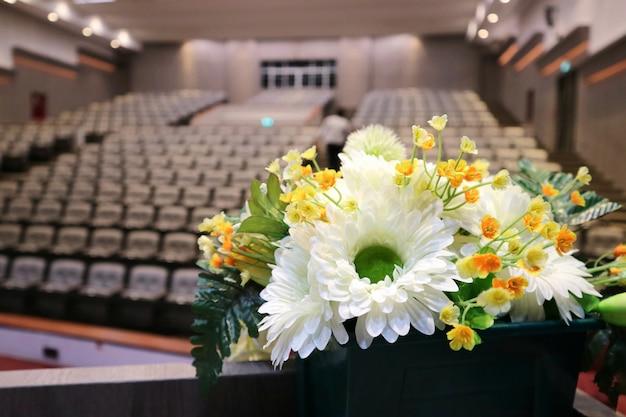Bukiet białych i żółtych kwiatów, dekoracja w sali konferencyjnej. koncepcja biznesu, edukacji i obiektu.