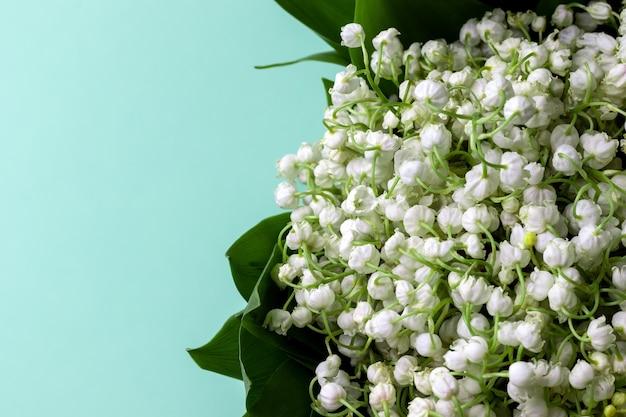 Bukiet białych konwalii w zielonych liściach na miętowym tle z kopią miejsca. selektywna ostrość. zamknąć widok