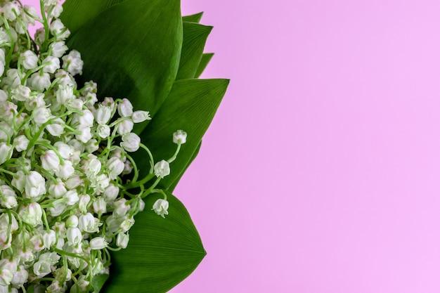 Bukiet białych konwalii w zielonych liściach na różowo z miejsca na kopię