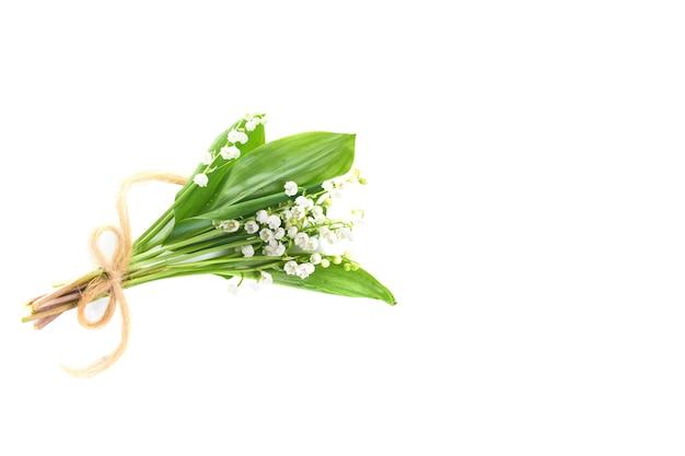 Bukiet białych kwiatów konwalii ze wstążką na białym tle