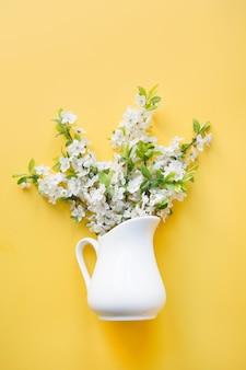 Bukiet białych kwiatów kwitnący wiśniowe drzewo owocowe w wazonie na żółty. widok z góry.