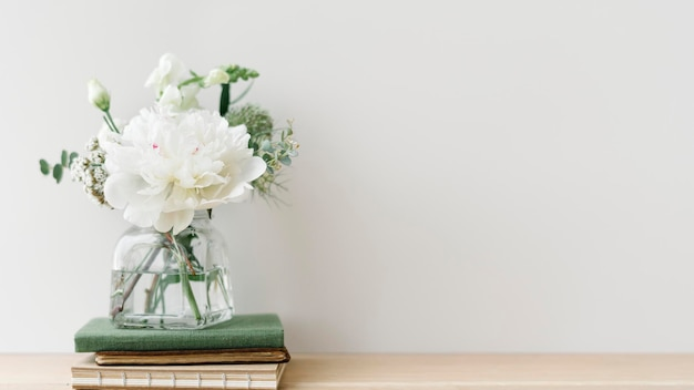 Bukiet białych kwiatów w oczyszczonym wazonie na stosie książek