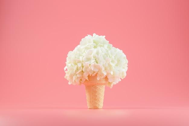 Bukiet białych kwiatów w rożku lodowym na różowo.
