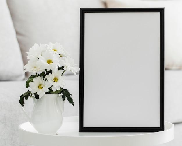 Bukiet białych kwiatów w wazonie z pustą ramką