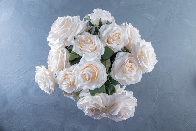 Bukiet białych kwiatów w wiadrze, na białym stole.
