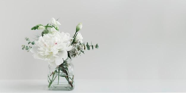 Bukiet białych kwiatów w wyczyszczonym wazonie