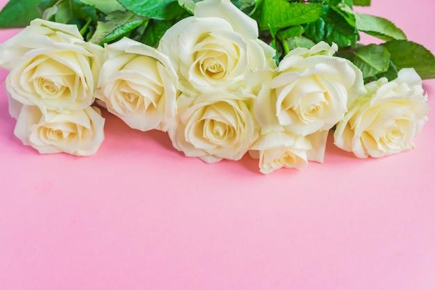 Bukiet białych kwitnących róż na pastelowym różowym tle. romantyczna ramka w kwiaty. skopiuj miejsce