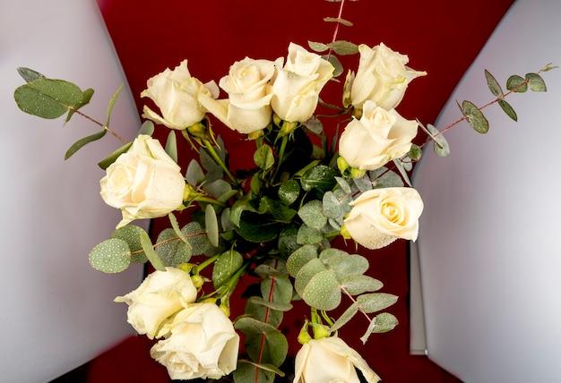 Bukiet białych róż i eukaliptusa z kroplami wody, widok z góry.