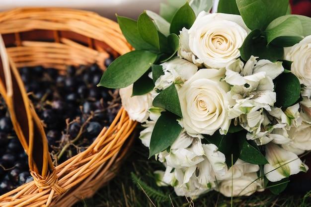 Bukiet białych róż leży obok kosza z winogronami.