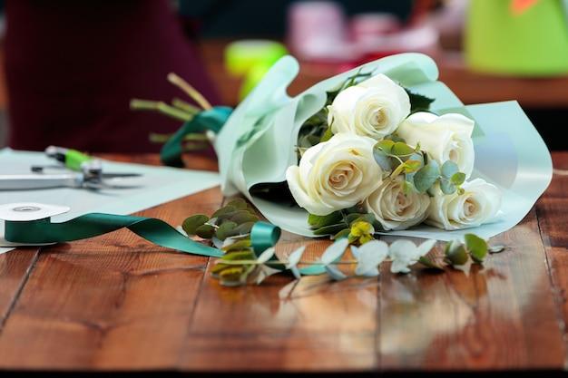 Bukiet białych róż w papierowym opakowaniu leży na drewnianym stole.
