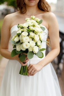 Bukiet białych róż w rękach panny młodej