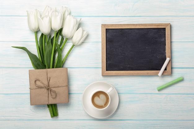 Bukiet białych tulipanów, filiżanka kawy z kredową deską i koperta na błękitnych drewnianych deskach. dzień matki