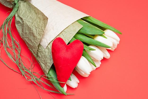 Bukiet białych tulipanów i czerwonego aksamitnego serca na czerwonym stole - koncepcja walentynek.
