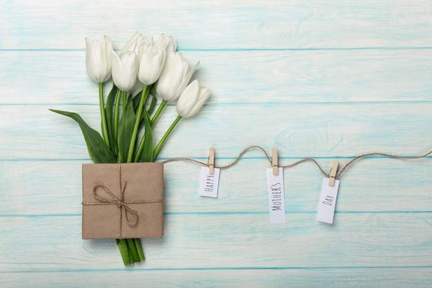 Bukiet białych tulipanów i koperty z naklejkami z bielizną na linie i niebieskie deski drewniane. dzień matki