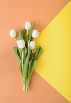 Bukiet białych tulipanów na mieszance żółtego i jasnobrązowego tła wiosennej koncepcji